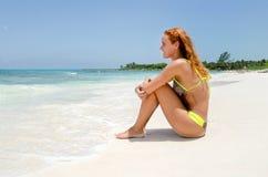 La fille s'asseyent à la plage photo stock