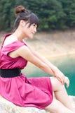 La fille s'asseyent au lac Image libre de droits