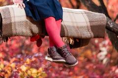 La fille s'asseyent sur le plaid dans la forêt d'automne photos libres de droits