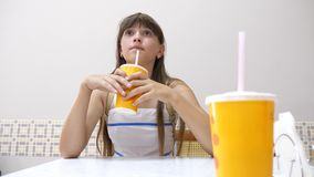 La fille s'assied à la table en café, boit un cocktail délicieux et sourit banque de vidéos