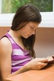 La fille s'assied à un hublot et affiche le livre Images libres de droits