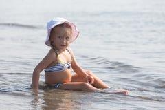 La fille s'assied au bord de l'eau Photographie stock