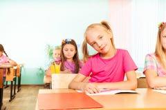 La fille s'assied au bureau avec des coudes sur le livre d'exercice Photographie stock libre de droits