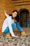 La fille s'assied au vieux mur de briques Image stock