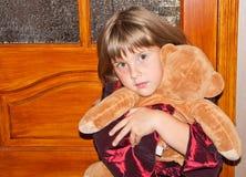 La fille s'assied avec le jouet Image stock