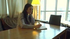 La fille s'assied dans le bureau, pense et écrit quelque chose dans un carnet banque de vidéos