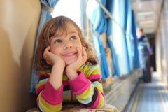 La fille s'assied dans le couloir du véhicule ferroviaire Photo stock