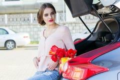 La fille s'assied dans le tronc de voiture avec des fleurs Photographie stock libre de droits