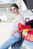 La fille s'assied dans le tronc de voiture avec des tulipes Images libres de droits