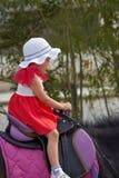 La fille s'assied dans la selle du ` s de cheval Image libre de droits
