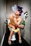 La fille s'assied dans une toilette Photographie stock