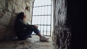 La fille s'assied derrière des barres à la fenêtre dans une forteresse en pierre Le foyer sur le mur, la fille est brouillé banque de vidéos