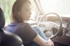 La fille s'assied derrière la roue d'une voiture Photographie stock libre de droits