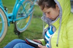 La fille s'assied en parc et lit un eBook image libre de droits