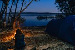 La fille s'assied pr?s du feu La tente campante bleue a illumin? ? l'int?rieur Terrain de camping d'heures de nuit R?cr?ation et  photo stock