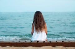 La fille s'assied regardant la mer avec elle de nouveau à la visionneuse Photos stock