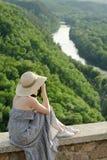 La fille s'assied sur la colline et prend des photos dans la perspective d'une forêt et d'une rivière de méandre Photo libre de droits