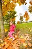 La fille s'assied sur des oscillations tenant les cordes en parc Photographie stock libre de droits