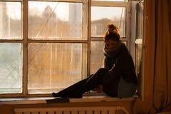 La fille s'assied sur la fenêtre images libres de droits