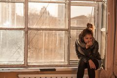 La fille s'assied sur la fenêtre photo libre de droits