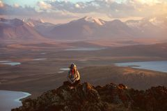 La fille s'assied sur la grande roche contre des montagnes et des lacs photos libres de droits