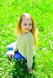 La fille s'assied sur l'herbe au grassplot, fond vert Concept d'apogée La fille sur le visage de sourire dépensent des loisirs de photo stock