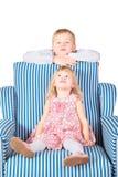 La fille s'assied sur la présidence. le frère est derrière Photographie stock