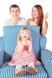 La fille s'assied sur la présidence, parents derrière la présidence. Images stock