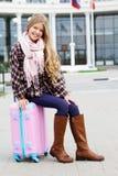 La fille s'assied sur la valise rose au-dessus de l'aéroport Photographie stock