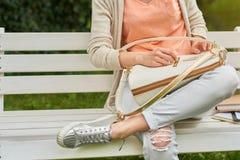 La fille s'assied sur le benck en bois avec un sac blanc Image stock