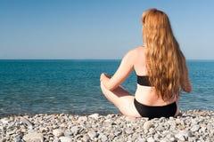 La fille s'assied sur le bord de la mer dans la pose de affaiblissement Image libre de droits
