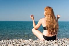 La fille s'assied sur le bord de la mer dans la pose de affaiblissement Photographie stock libre de droits