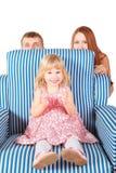 La fille s'assied sur le char, parents derrière elle Photographie stock libre de droits
