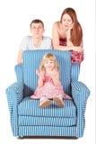 La fille s'assied sur le char. parents derrière elle Images libres de droits