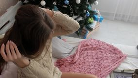 La fille s'assied sur le lit à côté de l'arbre de Noël L'atmosphère du ` s de nouvelle année banque de vidéos