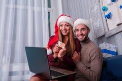 La fille s'assied sur le recouvrement d'un type avec un ordinateur portable Images stock