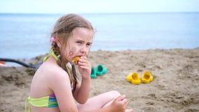 La fille s'assied sur le rivage arénacé près de l'eau et mange un petit pain Jour d'été chaud Vacances de famille à la mer banque de vidéos