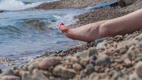 La fille s'assied sur le rivage de Baikal banque de vidéos