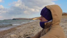 La fille s'assied sur le rivage de la mer et médite Vagues, beau paysage clips vidéos
