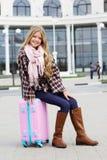 La fille s'assied sur le sac rose de voyage au-dessus de l'aéroport Photos stock