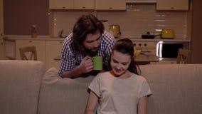 La fille s'assied sur le sofa et travaille avec le comprimé Le type vient de la cuisine et des stoppes derrière la femme Il tient banque de vidéos