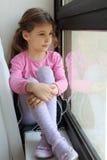 La fille s'assied sur le windowsill et regarde à l'extérieur l'hublot Images stock