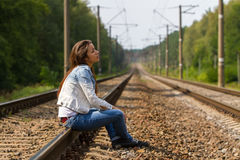 La fille s'assied sur les rails images stock