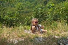 La fille s'assied sur la montagne et examine la distance photo libre de droits