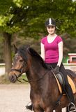 La fille s'assied sur son poney Photos stock