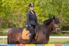 La fille s'assied sur son poney Photo stock