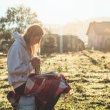 La fille s'assied sur un banc en bois dans les montagnes en nature, lit un livre, boit du thé chaud d'une tasse thermo Concepts l image stock