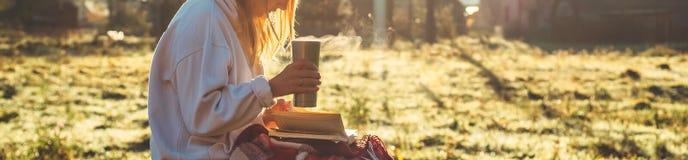 La fille s'assied sur un banc en bois dans les montagnes en nature, lit un livre, boit du thé chaud d'une tasse thermo Concepts l photo libre de droits