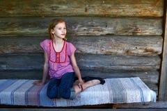 La fille s'assied sur un porche du woode Image libre de droits