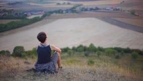 La fille s'assied sur une colline et examine la distance clips vidéos
